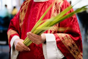 Deacon in red dalmatic carrying palm branches